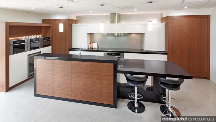 A modern kitchen with a black and timber design