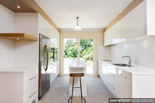 A streamlined white kitchen with a glossy finish designed by Alby Turner & Son Kitchens