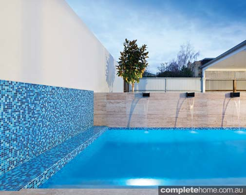 An outdoor pool with a clean design by Liquid Blue Pool & Spa Design
