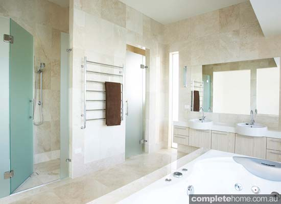 A modern bathroom featuring a frameless shower screen