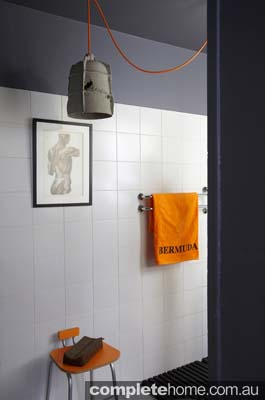 Eclectic and vintage bathroom with an orange flare in an apartment in Paris.