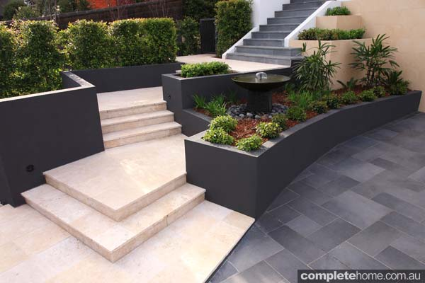 Tropical and formal elements collide in this landscape design from Cool Water Landscapes.