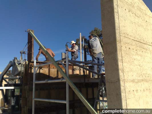 Builders working on a rammed earth house.