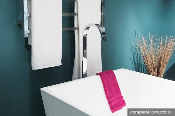 A sleek white bath with a pink towel.