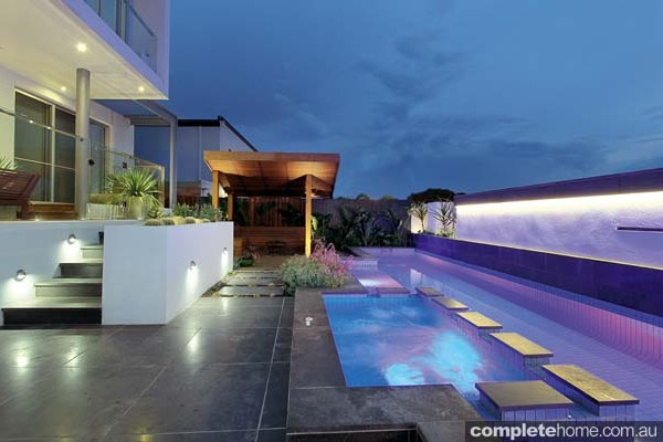 A stunning modern pool from Baden Pools illuminated at night.