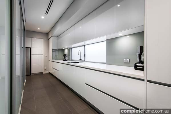A contemporary kitchen with pure white stone benchtops.