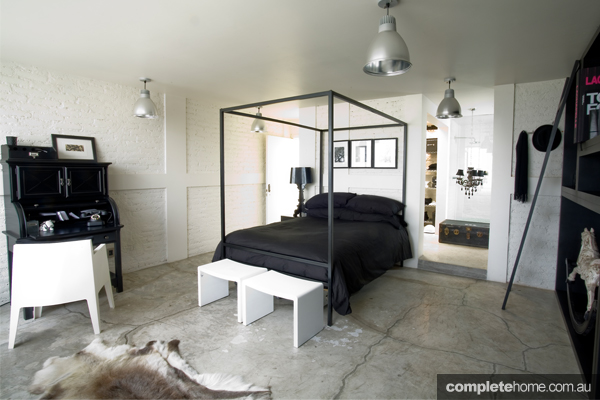 A modern bedroom with concrete flooring.