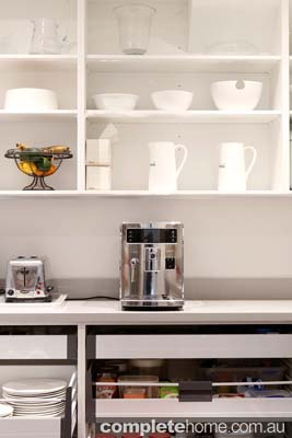 A sleek coffee maker in a contemporary butler's pantry.