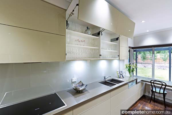 Electric bi-fold cabinet doors in a designer kitchen from Kitchens by Peter Gill.