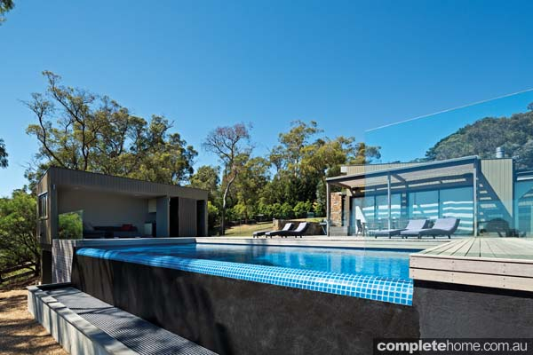 A modern pool design from Aquarius Pools with a frameless glass fence,