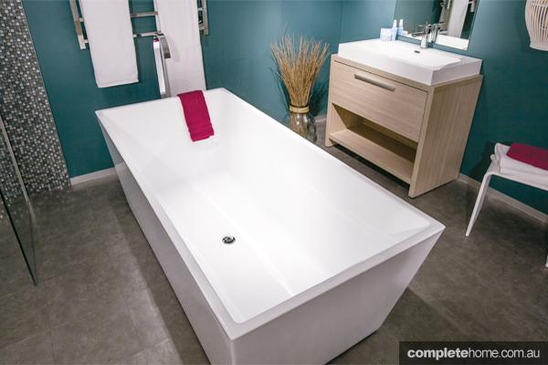 A sleek white bathtub in a modern bathroom.