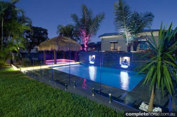 A tropical resort-style pool lit with LED lights from Malibu Pools.
