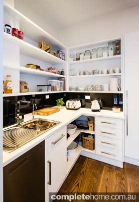 A white butler's pantry in an elegant minimalist kitchen design.