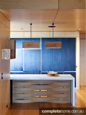 A kitchen with a blue wall in a modern timber tree house.
