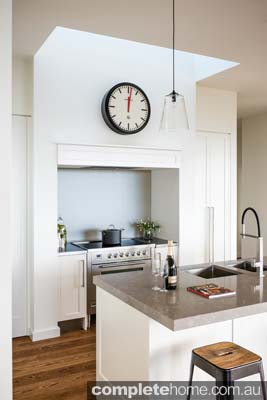 The large clock becomes a main feature in this white minimalist kitchen.