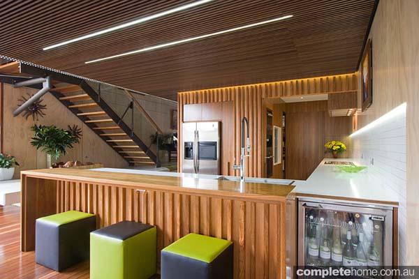 Timber kitchen featuring plush green bar stools.