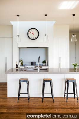 A white minimalist kitchen design with american oak flooring.