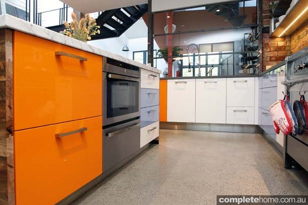 These orange draws make a bold statement on these kitchen cabinets.