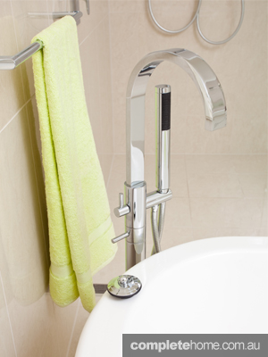 A white freestanding bathtub, stainless steel tap and green towel.