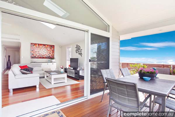 The balcony and living area of a light and traditional beach house from Classic Country Cottages.