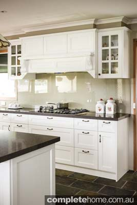 kitchen of white and neutral colouring, with slate tiles, wooden accents, stainless steel appliances and antique handles