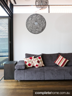 contemporary lounge room with grey sofa and metal orb light fitting