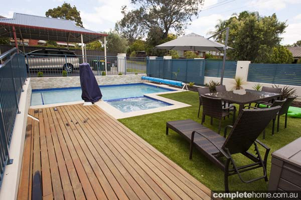 jade swimming pool design with sandstone paving and decking