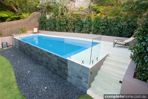 floating blue pool with sandstone paving and glass side