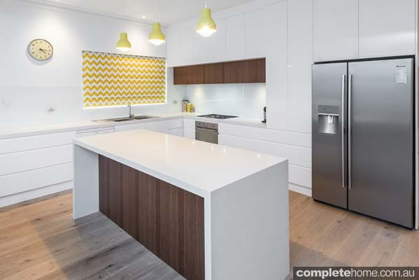Modern white gloss kitchen design with timber finishings and stainless steel appliances