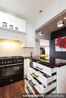 kitchen renovation and storage solution ideas with white cabinetry, vintage handles and black caeserstone benchtop