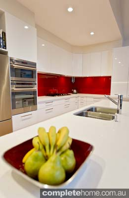 kitchen design ideas with a red splashback, gloss white cabinetry, stainless steel appliances and timber flooring