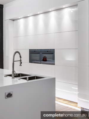 designer kitchens kitchen ideas with gloss white cabinetry, timber flooring and stainless steel accessories