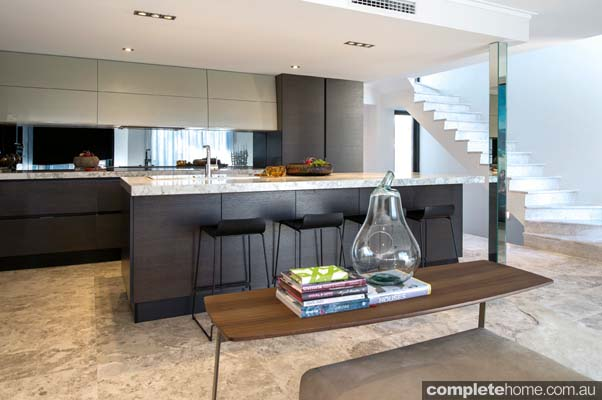 The clever use of reflective surfaces creates strong visual impact, with the mirror splashback and shiny stainless-steel appliances reflecting natural light and stunning ocean views.