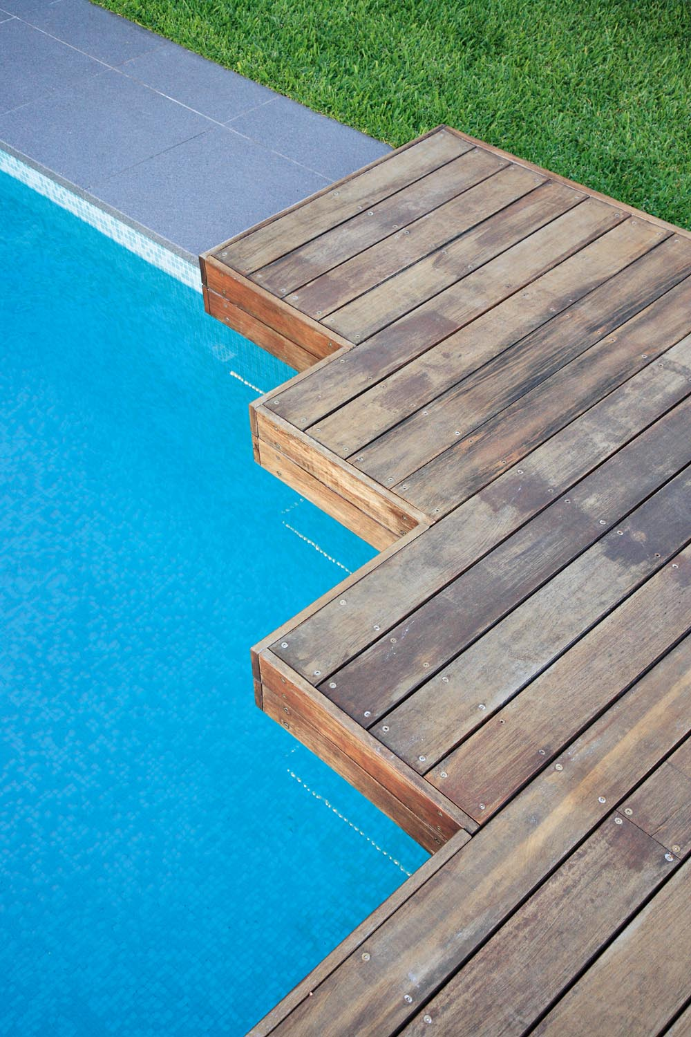 Pool corner with wooden platform and lawn