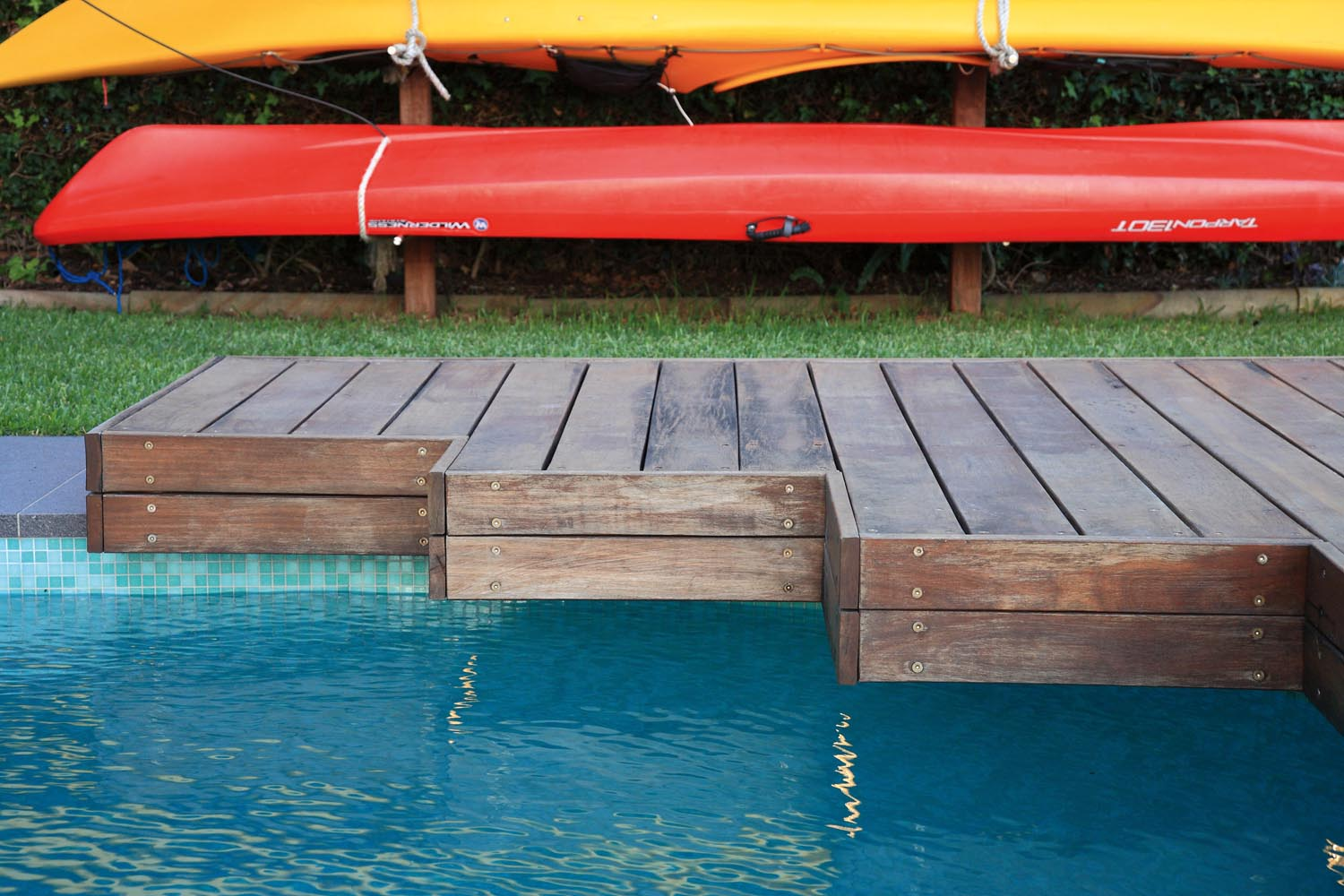 Pool corner with wooden platform and a red kayak