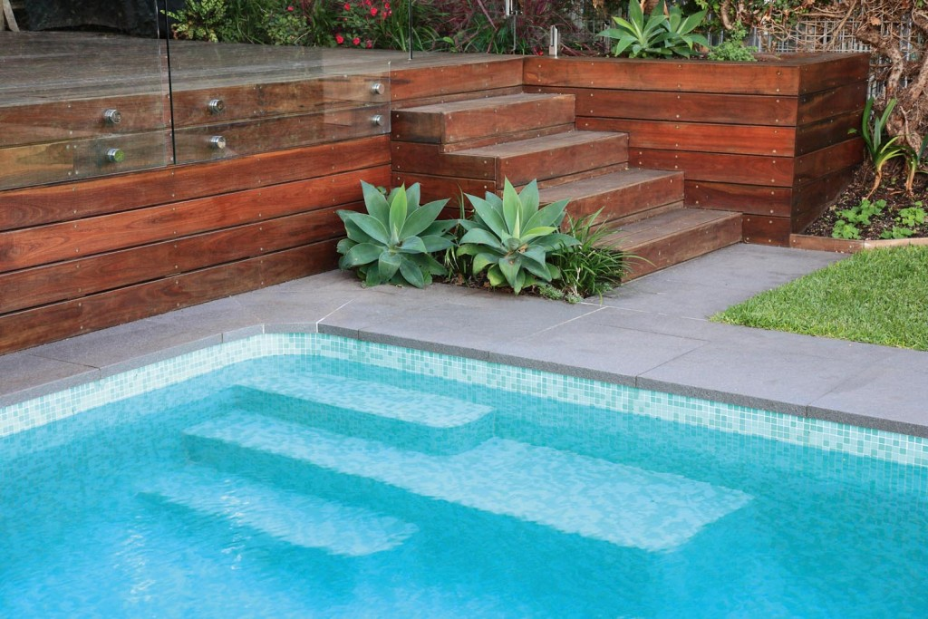 Corner of a pool with wooden stairs and succulent plants