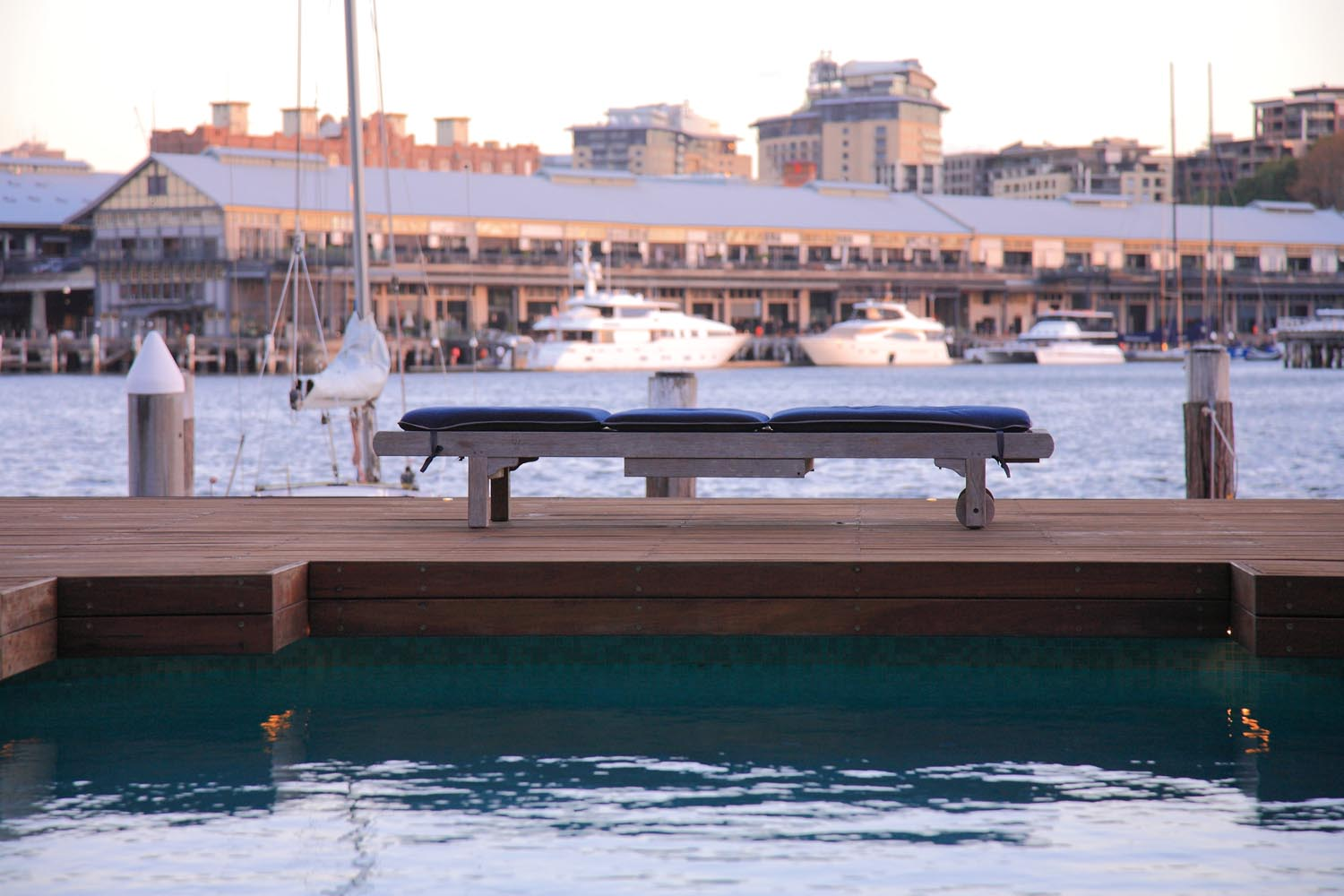 Close up of outdoor furniture next to a pool with a view of buildings behind across a river
