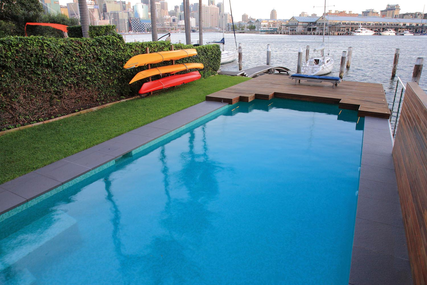 Simple pool with kayaks and a view of the city