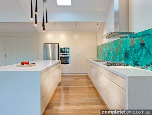 We love the acrylic couture malachite green splashbacks, which add intense colour and drama to the open kitchen.