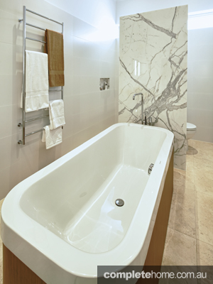 We love the feature stone splashback behind the bath.