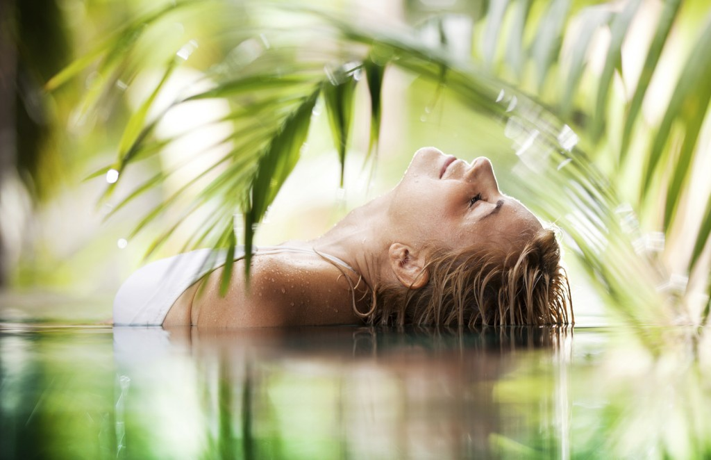 Side view of a beautiful woman lying in the tropical pool .  [url=http://www.istockphoto.com/search/lightbox/9786750][img]http://img291.imageshack.us/img291/2613/summerc.jpg[/img][/url]