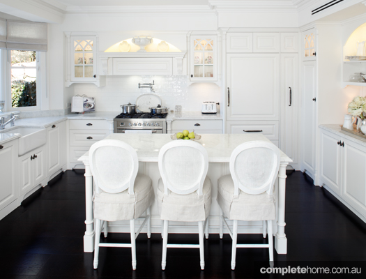 Contrasting white cabinetry against deep chocolate flooring, this federation-style kitchen is complimented by every detail
