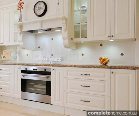 with a custom built mantel and cap moulding this kitchen is given