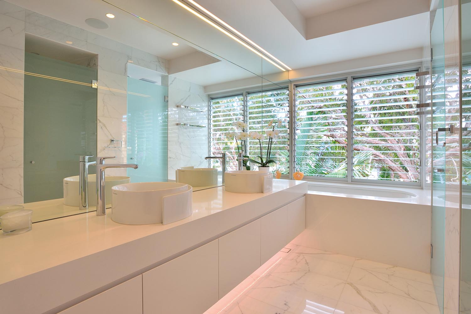 The white and stone theme is carried throughout the house to the bathroom