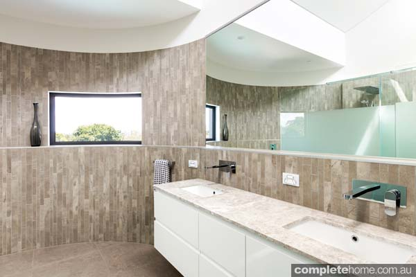 A glorious curved wall and contrasting features and textures create a fabulous ambiance in this bathroom design
