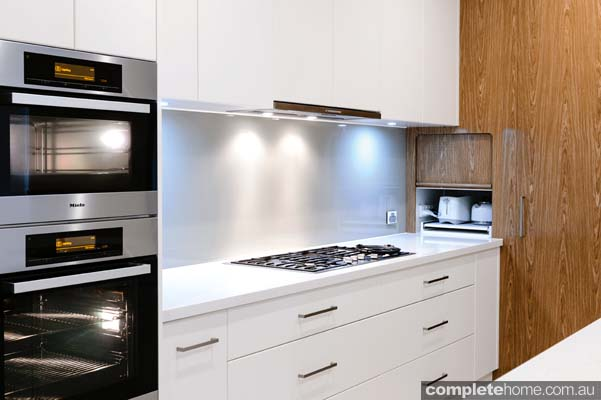 Use angled walls to your advantage by installing cabinets against them and by using integrated appliances