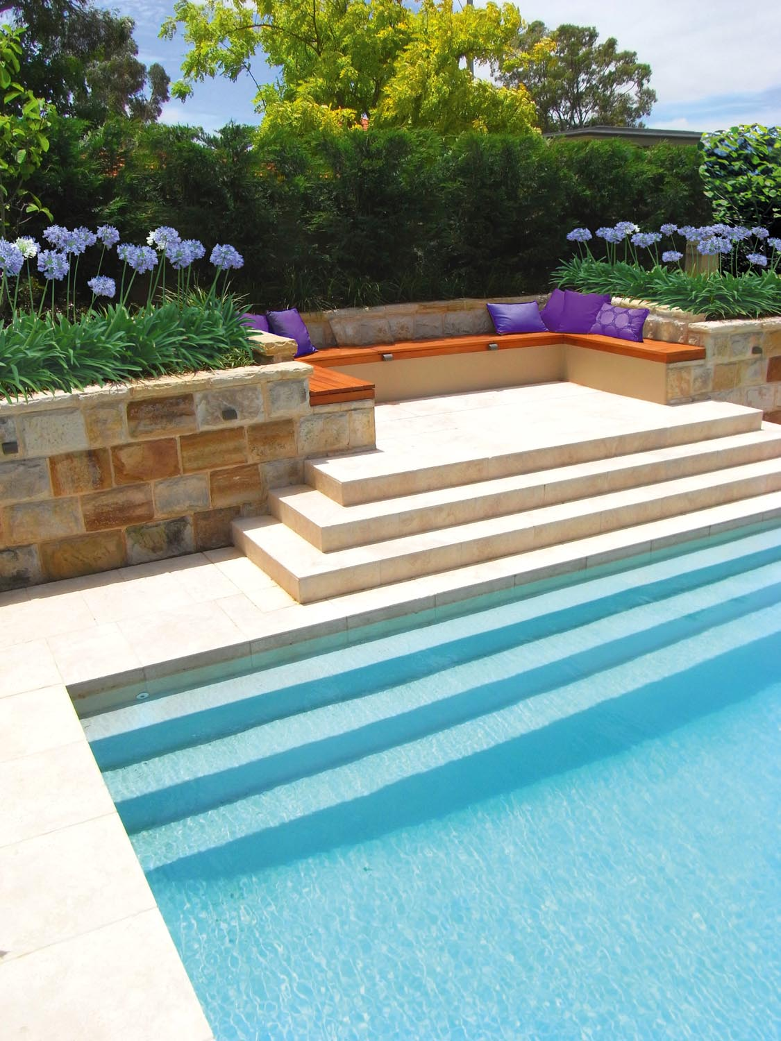 Modern pool corner with sandstone wall and flowers