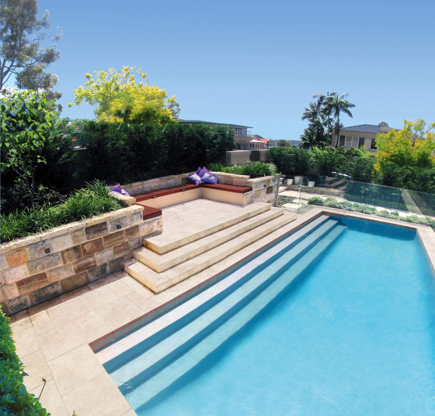 A modern pool with descending steps along the way surrounded by a garden