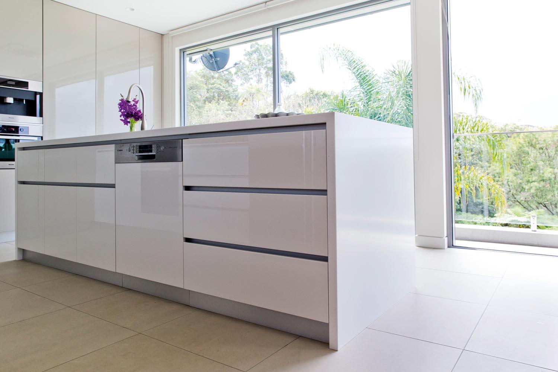 A white sleek kitchen with big windows