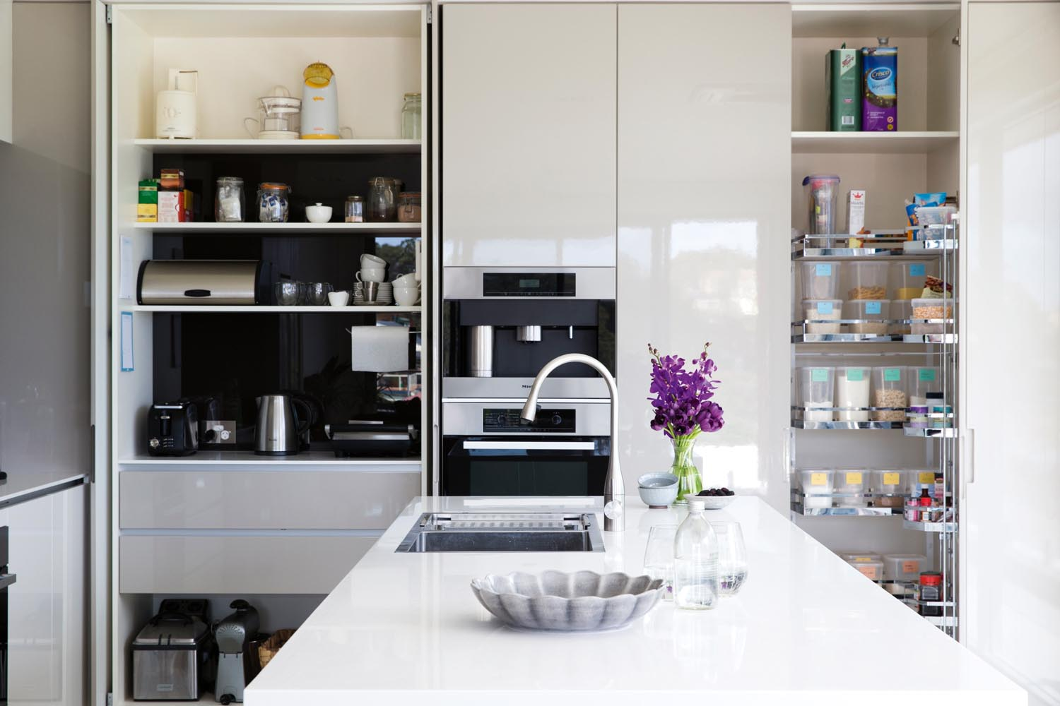 A white modern kitchen with a tap and flowers